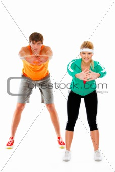 Fit young woman and man in sportswear making sport exercise isolated on white
