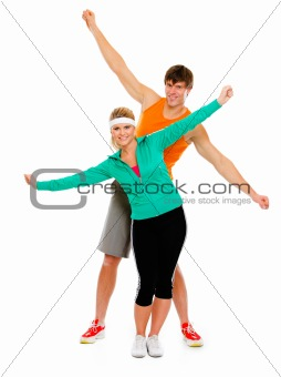 Fit girl and man in sportswear having fun isolated on white