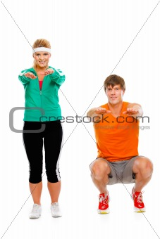 Portrait of healthy girl and man in sportswear sitting on squat isolated on white