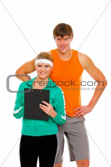 Portrait of young man and fit girl in sportswear with clipboard isolated on white