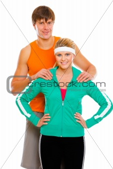 Portrait of happy young man and fitness girl in sportswear isolated on white