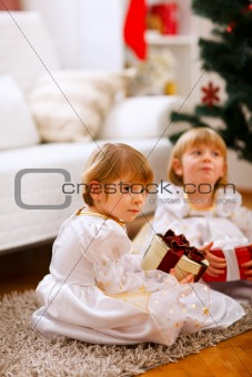 One of twins girl sitting with present with serious expression
