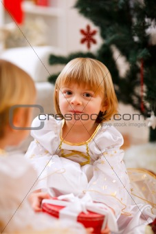 Two happy twins girl sitting with presents near Christmas tree