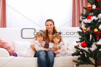 Portrait of mother with two twins daughters near Christmas tree