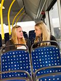 Two young women chatting on the bus