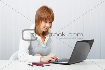 Attractive girl with a laptop in the office