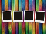 four blank photos on colorful wooden background