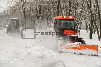 Two tractor snow removal in the park
