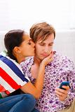 Girl trying to distract her busy boyfriend from mobile phone