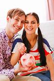 Portrait of happy young couple putting coin in piggy bank