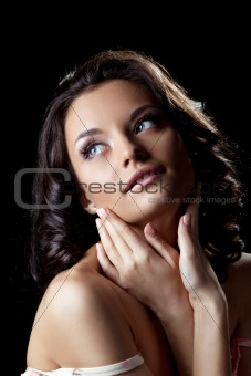 cute young woman posing with hands in dark