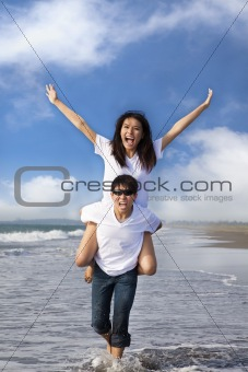 happy couple running in the water at the beach