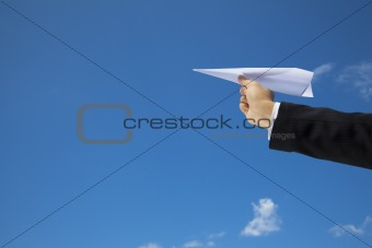 hand of Businessman letting an airplane made of paper fly over blue sky