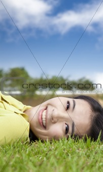 smiling asian young woman on the grass