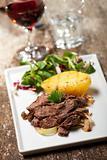 sliced sirloin steak on a plate with salad