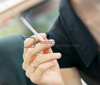 Cigarette smoking in women's hand. Soft focus.