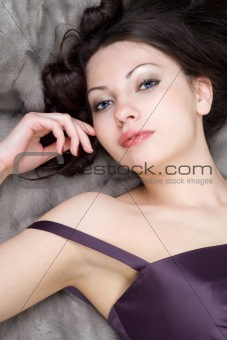 Young woman lying on grey fur coat