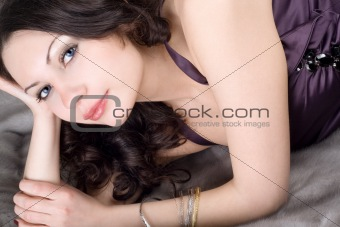 Beautiful young woman lying on grey fur coat