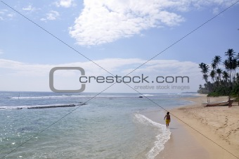 A man walking down the beach on a bright sunny day