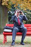 Businessman searching with binoculars