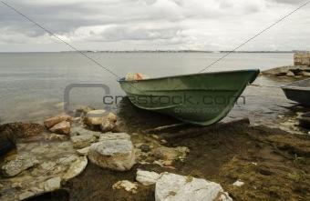 Green fishing boat on seacoast