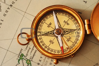 Antique brass compass over old Canadian map