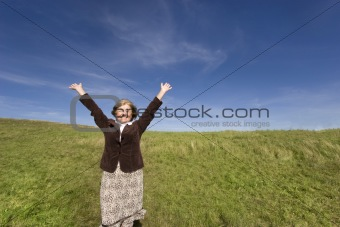 Attractive mature woman enjoying life on the meadow