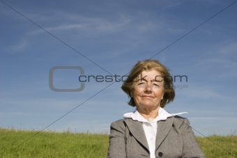 Beautiful, joyful mature woman on the meadow