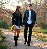 Young happy couple in love walking in park holding hands