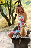 Young beautiful woman and a cat sitting on the bench