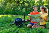 Young couple tourist with map in hand sitting on the grass