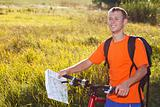 Happy man cyclist with map in hand