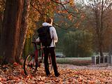 Woman cyclist with bike and backpack in autumn park on the morni