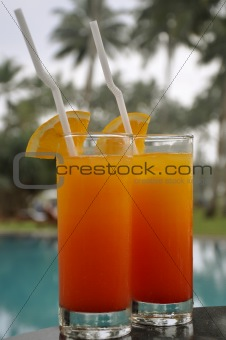 Two Glasses of Tequila Sunrise by a Pool