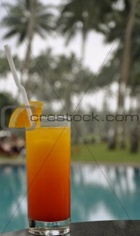 A Glass of Tequila Sunrise by a Pool