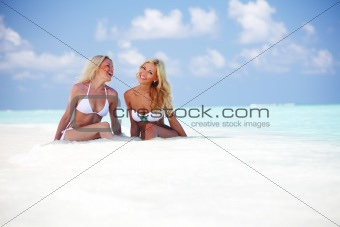 girls sitting on ocean coast