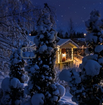 Illuminated house on snowy Christmas evening