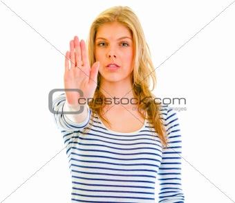 Portrait of serious teen girl showing stop gesture