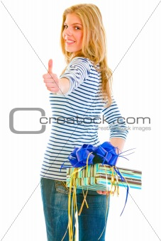 Smiling beautiful teen girl hiding present box behind back and showing thumbs up