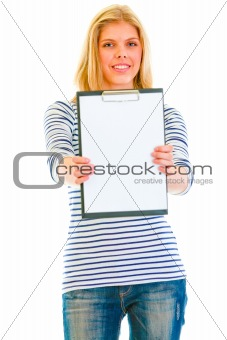 Smiling beautiful teen girl showing blank clipboard