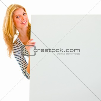 Portrait of teen girl holding blank billboard