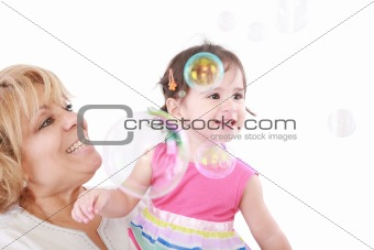 Aunt and a little girl enjoy looking at bubbles floating in the