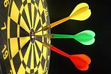 Three colourful darts in the bullseye.