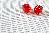 Two red dice on a spreadsheet financial data print out.