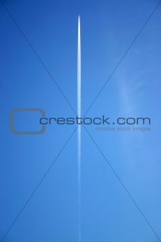 A jet flying overhead with jet trails.