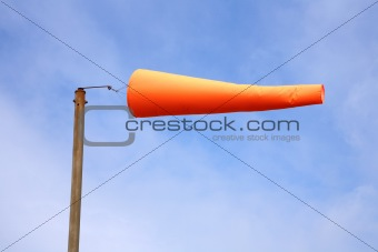 An orange windsock, blowing in a strong wind.