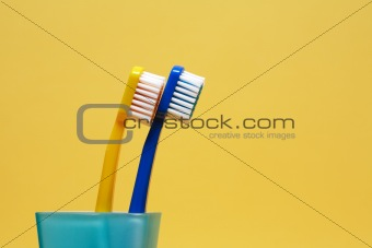 Toothbrushes On Yellow