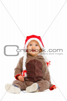 Portrait of cute baby in Santa hat looking up