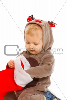 Curious cute baby examines Christmas sock