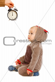 Cute baby in costume of Santa Claus&#39;s reindeer looking on alarm clock